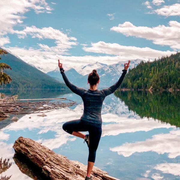 Woman doing yoga tree pose at Cheakamus Lake in Whistler